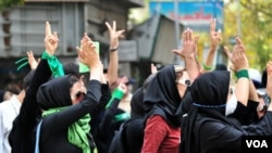 Iran - Iranian women hold up their hand and chant slogans during a protest against result of the presidential election on 2009 in Tehran . UNDATED