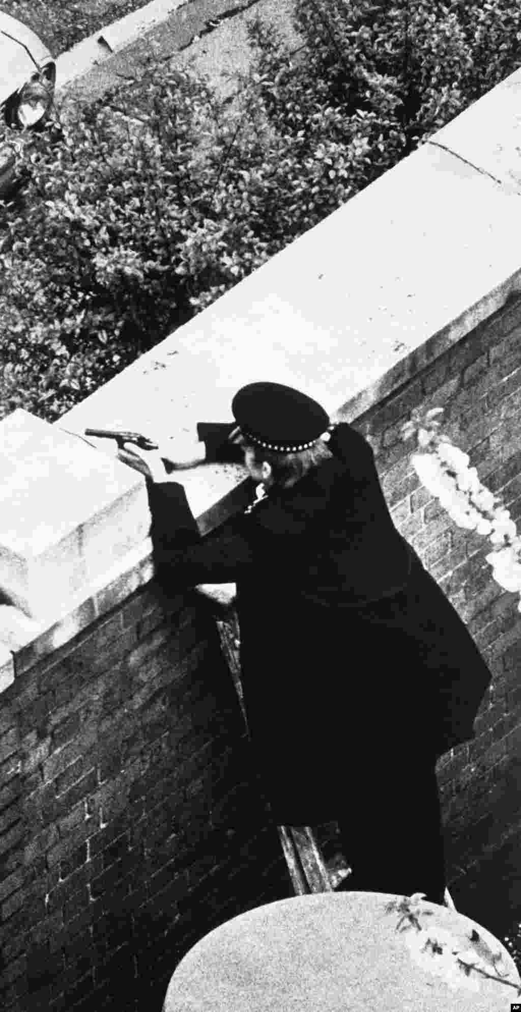 An armed police officer points his handgun toward the Iranian Embassy in London on the first day of the siege, April 30, 1980. The six gunmen demanded that Arab prisoners in Iran's Khuzestan Province be released and that their own safe passage out of the United Kingdom be guaranteed. The British government quickly rejected the demand for safe passage and a siege ensued.