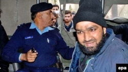Pakistani security officials detain Mumtaz Hussain Qadri, right, one of their colleagues who allegedly killed Salman Taseer, the governor of Pakistan's most populous province of Punjab, in Islamabad in January 2011.