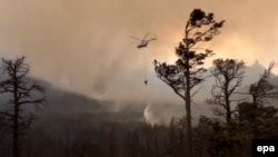 An image released by the Russian Emergency Situations Ministry on August 12 shows a helicopter dropping water onto a forest fire in the Baikal lake area in Irkutsk.