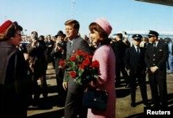 Жон Кеннеди жубайы Жаклин менен Техас штатынын Даллас шаарындагы Лав-Филд аба майданында (президент киши колдуу болуп өлөрдөн 1 сааттай мурдараак тартылган сүрөт). 22-ноябрь, 1963-жыл.