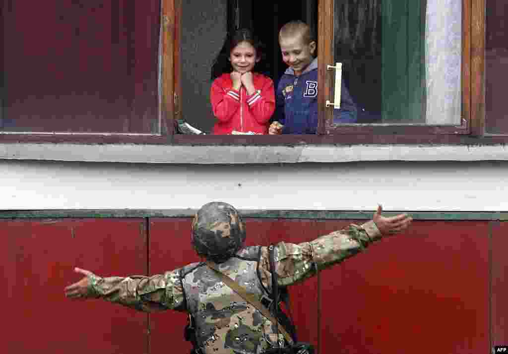 A Ukrainian soldier gestures as he talks with children on August 18 in the small eastern city of Popasna in the Luhansk Region. (AFP/Anatolii Stepanov)