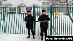 Russian police officers guard the entrance to a Moscow school building after receiving a report that a student was threatening to injure himself with a knife on December 6.