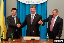 Президент Петр Порошенко жмет руки новому министру иностранных дел Павлу Климкину (слева) и бывшему министру иностранных дел Андрею Дещице. Киев, 19 июня 2014 года.