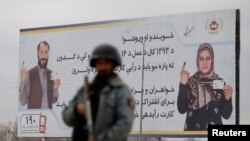 A policeman stands near a billboard for the presidential election at a checkpoint in Kabul, April 4, 2014.