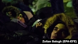 A group of migrants rest in the Serbian village of Kelebia, bordering Hungary, on February 7.