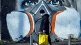 ITALY -- A man walks with his groceries beside a mural painting that portrays a person wearing a gas mask, Milan, Italy, 16 March 2020.