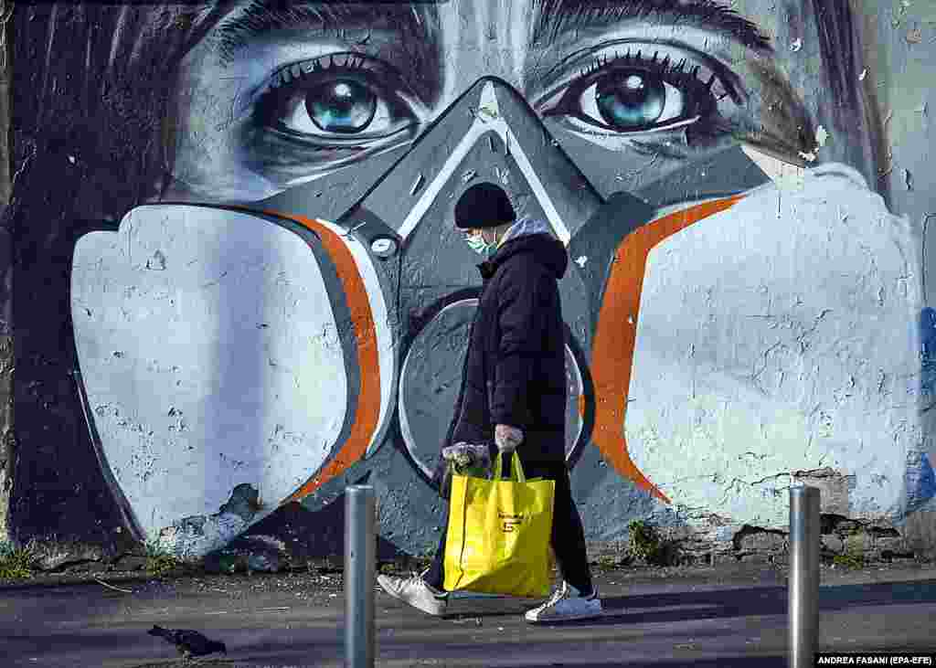 An Italian man wearing a face mask walks with his groceries past a mural in Milan that portrays a person wearing a gas mask.