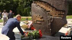 Russian President Vladimir Putin lays flowers at the monument to the sailors who died in the disaster in the city of Kursk in August 2003.