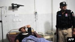 Një polic pakistanez qëndron afërt kolegut të plagosur sot në periferi të Peshavarit