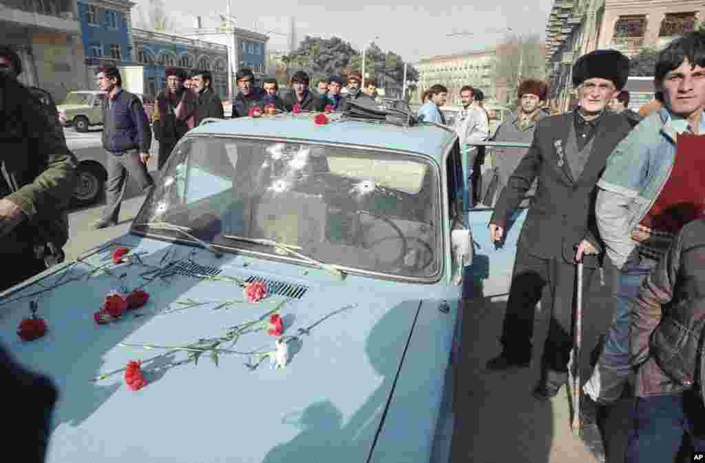Baku residents lay flowers in honor of those who were killed in the Soviet crackdown. This car's windshield was riddled with bullet holes.