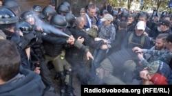 Силовик «поливає» себе зі сльозогінного балончика під час сутичок поліції та активістів під будівлею Генпрокуратури, Київ, 17 вересня 2018 року