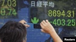 Japan - A man takes a picture of a stock index board with his mobile phone outside a brokerage in Tokyo, 09Aug2011