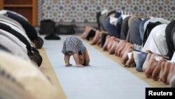 Ребенок рядом с молящимися членами мусульманской общины во время полуденной молитвы в мечети Страсбурга. 9 июля 2013 года.