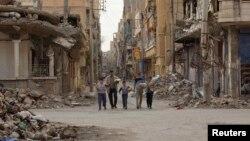 Сирієць із дітьми йде вулицею міста Дейр ез-Зор, 13 березня 2013 року