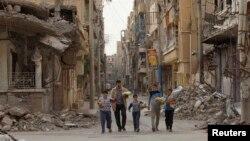 Жители сирийского города Дейр аз-Зор возвращаются после того, как получили хлеб, который раздают гуманитарные организации