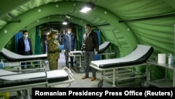 Romanian President Klaus Iohannis inspects a mobile military hospital that will tend to patients infected with the coronavirus in Otopeni, near Bucharest, on March 28.