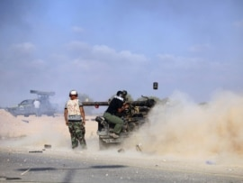 NTC fighters shoot artillery at a pro-Qaddafi position in Sirte on September 18.