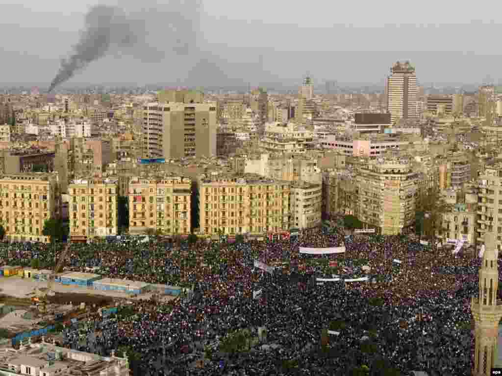 Smoke rises from an unknown location as protesters rally in Tahrir Square.