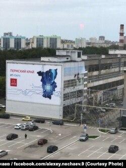 """Цеха """"Мориона"""" перед приездом Путина - баннер с проспектом в Пекине еще не повесили, но каркас для него уже смонтировали. На фото рабочие закрывают от взгляда президента еще одним баннером верхний этаж цеха слева"""
