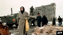 Chechnya -- Chechen women and men pass by a Russian armoured personnel carrier in front of the destroyed presidential palace in Grozny. Feb1996.