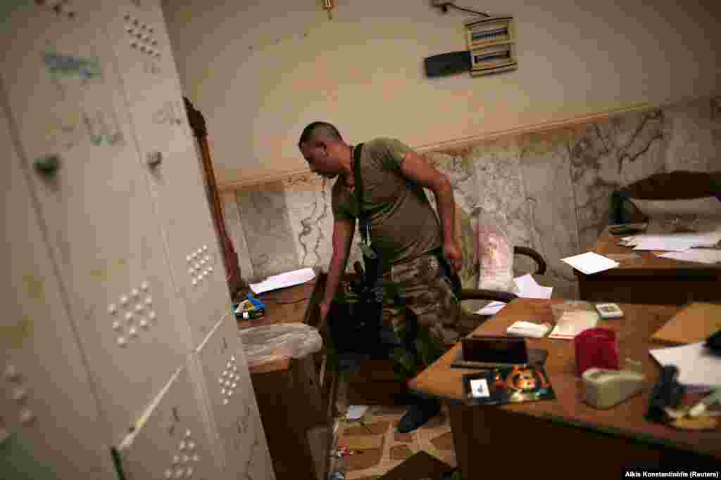 Discarded children's textbooks and toys inside a room being searched by an Iraqi soldier. As of June 6, Islamic State militants reportedly control just 4 square kilometers of Mosul.