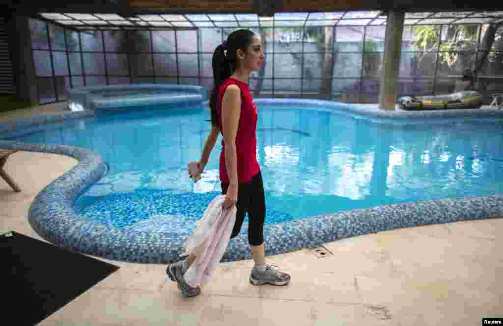 Educator and model Fatima walks past a swimming pool after working out in a gym in her home in Lahore. Fatima is the chief executive officer of the Beaconhouse School System, a network of private schools founded by her mother-in-law.