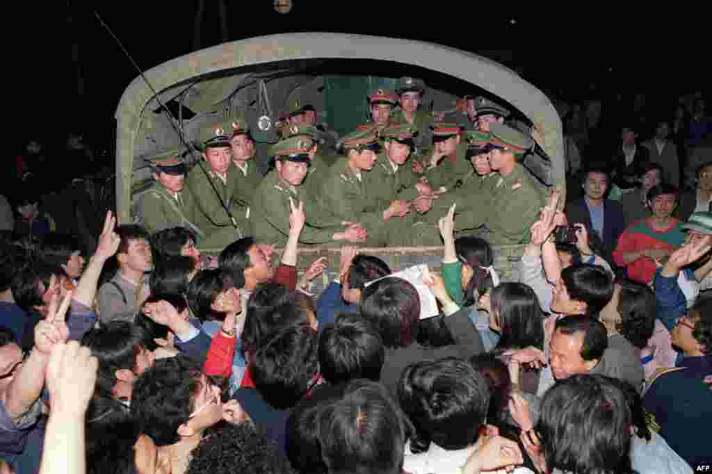 Demonstrators raise their fists and flash victory signs as they stop a military struck on its way to Tiananmen Square shortly after martial law was declared on May 20, 1989.