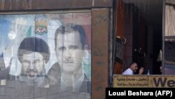 A poster bearing an image of Syrian President Bashar al-Assad (right) and Hassan Nasrallah, head of the Lebanese Shi'ite movement Hizballah, is seen in Damascus.