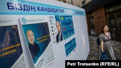 A woman walks past election posters of Kazakh presidential candidates Qasym-Zhomart Toqaev and Amangeldi Taspikhov. Almaty, 14May2019