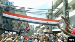 A video grab shows Syrian protesters waving a national flag in Latakia.