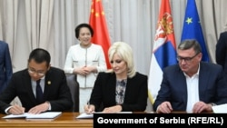 Serbian Construction Minister Zorana Mihajlovic (center) signs a contract with a Chinese company to build new stretch of road in western Serbia.