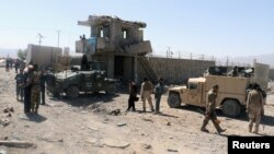 Afghan security forces inspect the aftermath of a suicide bomb blast in Paktia Province on June 18.