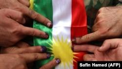 Бійці курдського ополчення «пешмерґа» на тлі національного прапора показують свої позначені чорнилом пальці після голосування на референдумі 25 вересня