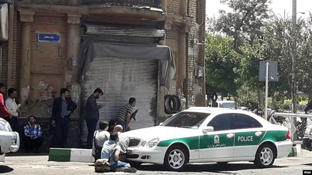 Journalists and police crouch near the Iranian parliament in the capital Tehran during an attack on the complex that left at least a dozen people dead.