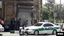 Journalists and a police vehicle at the scene outside Iranian parliament in the capital Tehran during an attack on the complex, 07Jun2017