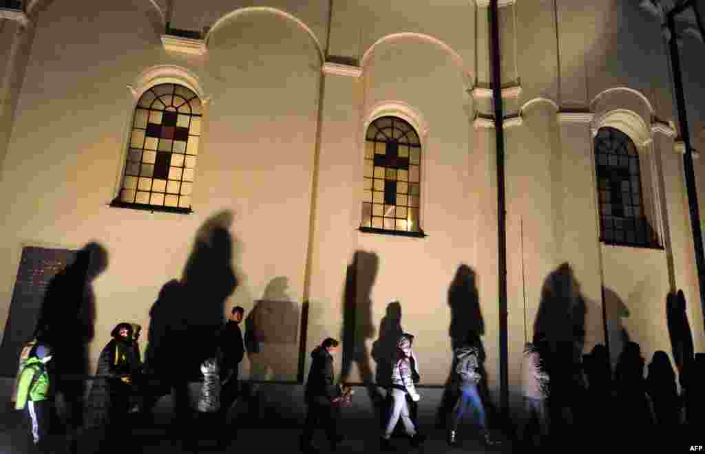 People walk past a church in the Serbian city of Sabac, 80 kilometers west of Belgrade, during an Orthodox Christmas Eve ceremony. (AFP/Andrej Isakovic)
