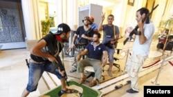 """Адватчылар """"Rixos"""" мейманканасында Каддафинин портретин тепселеп турушат. Триполи. 24-август, 2011-жыл."""