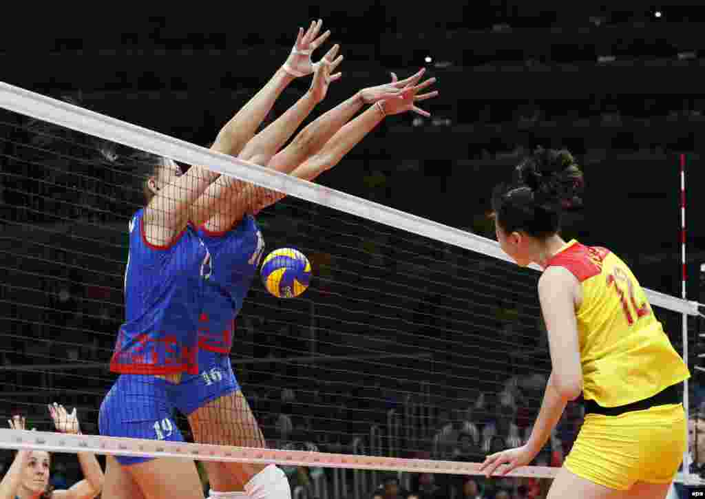 China's Ruoqi Hui (right) spikes the ball during the women's volleyball gold-medal match between China and Serbia. China won 3:1.