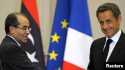 Ливия Ұлттық өтпелі кеңесінің жетекшісі Мұстафа Абдул Жалил (сол жақта) және Франция президенті Николя Саркози. Париж, 24 тамыз 2011 ж.