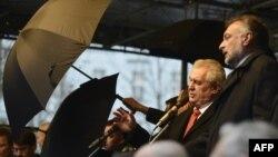 Ахоўнікі трымалі парасоны, калі людзі кідалі яйкі і памідоры ў прэзыдэнта Чэхіі Мілаша Зэмана 17 лістапада 2014 году.