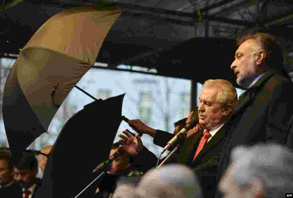 Security guards hold up umbrellas as people throw eggs and tomatoes at Czech President Milos Zeman (center) before the unveiling of a plaque on the 25th anniversary of the Velvet Revolution. Protestes are upset with Zeman's pro-Russian stance and his use of foul language in public. (AFP/Rene Volfik)