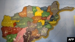 An election worker sits under a map of Afghanistan in Mazar-e Sharif.