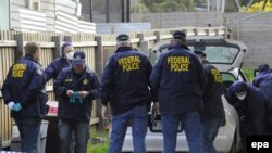 Australian forensic police inspect a car at a house in Melbourne.