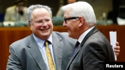 Greek Foreign Minister Nikos Kotzias (left) and his German counterpart, Frank-Walter Steinmeier, attend the extraordinary European Union foreign ministers meeting in Brussels on January 29.