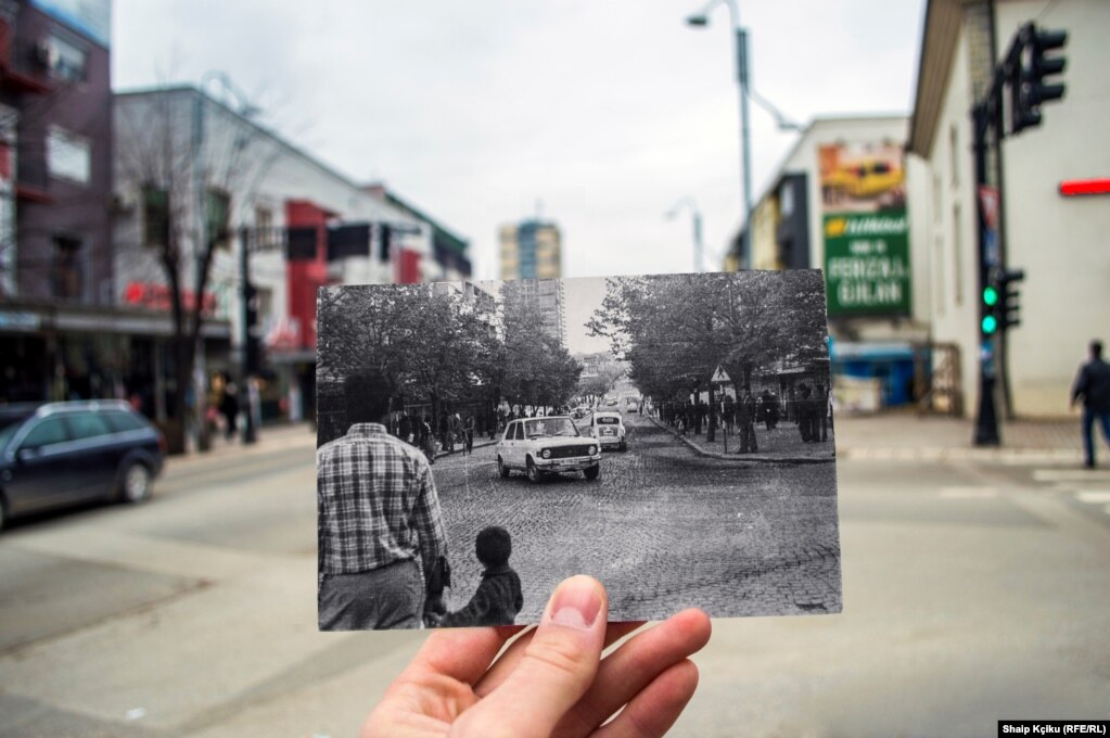 "Shaip Kçiku got out of bed extra early that day. He told RFE/RL, ""I wanted to make sure the streets were empty to take the photo."" The print he's holding shows the Gjilan neighborhood as it looked in the 1970s."