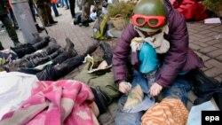 Активіст пише ім'я на нозі убитого демонстранта в Києві, 20 лютого 2014 року