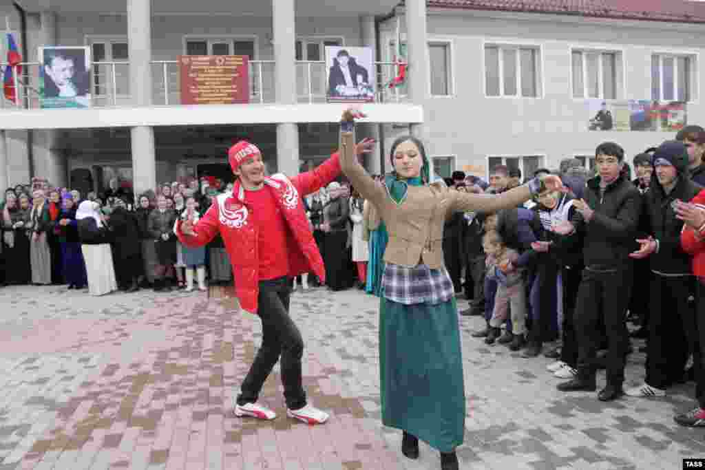 A young man and woman dance outside a polling station in Grozny during Russia's presidential election in March 2012.