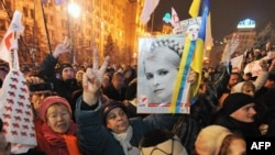 A man flashes a victory signs as he holds a portrait of jailed ex-premier Yulia Tymoshenko during a rally in Kyiv on November 22.