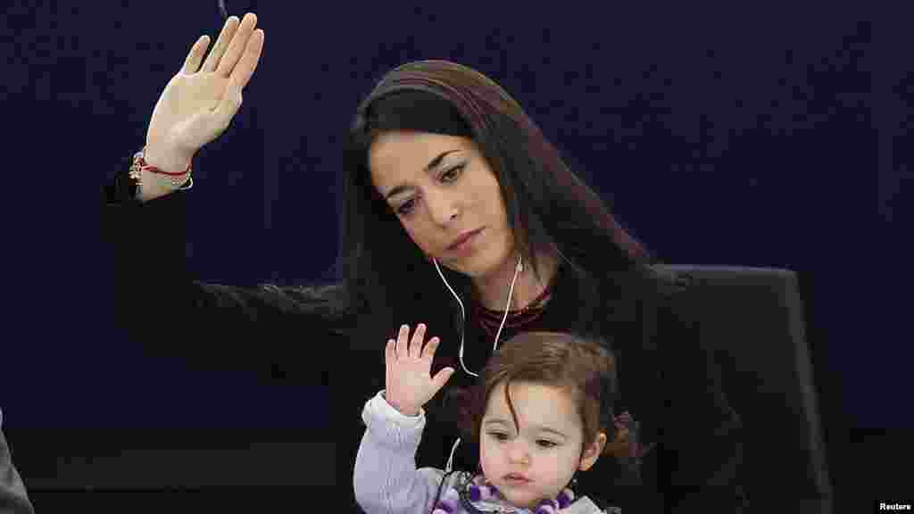 Licia Ronzulli, an Italian member of the European Parliament, takes part with her daughter in a voting session at the European Parliament in Strasbourg. (Reuters/Vincent Kessler)